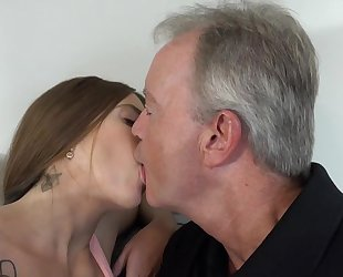 Sex-starved brunette pleasuring old man on the sofa